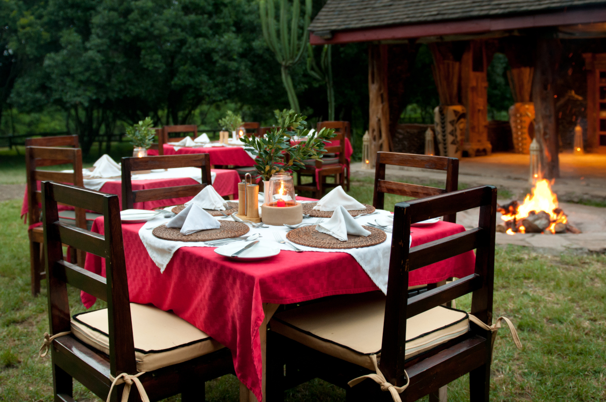 Dining tables around firepit at river lodge